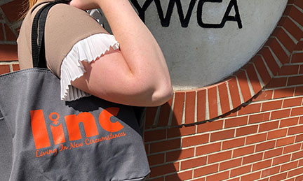 Woman carrying LiNC tote bag by the YWCA sign